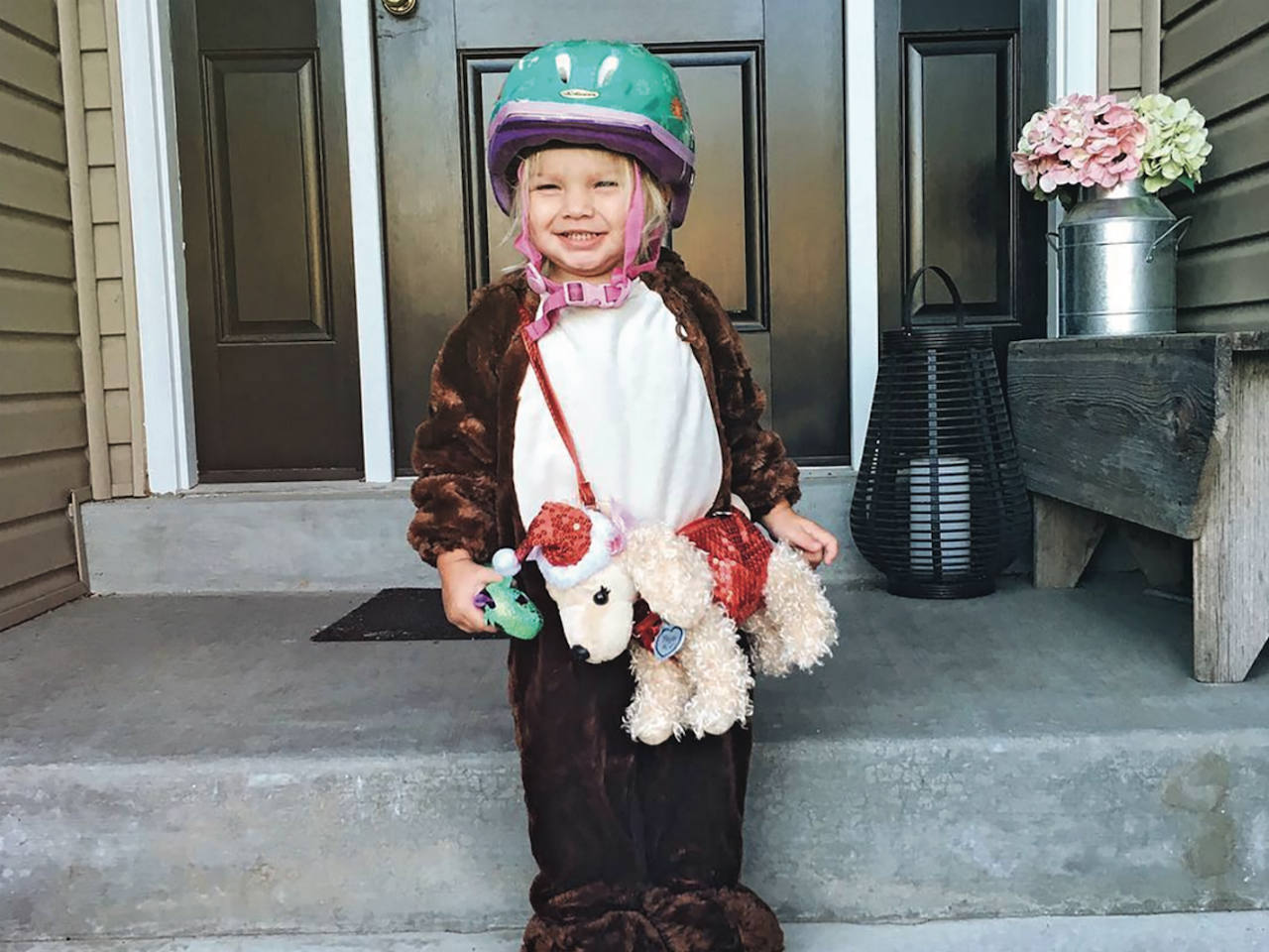 A little girl on the front steps of her house dressed in a furry costume and bike helmet