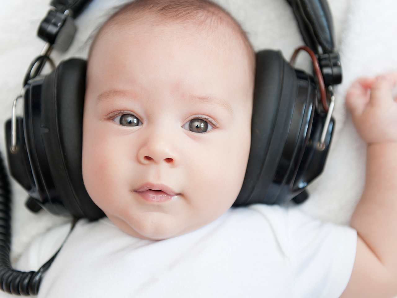 Baby wearing headphones too big for its head