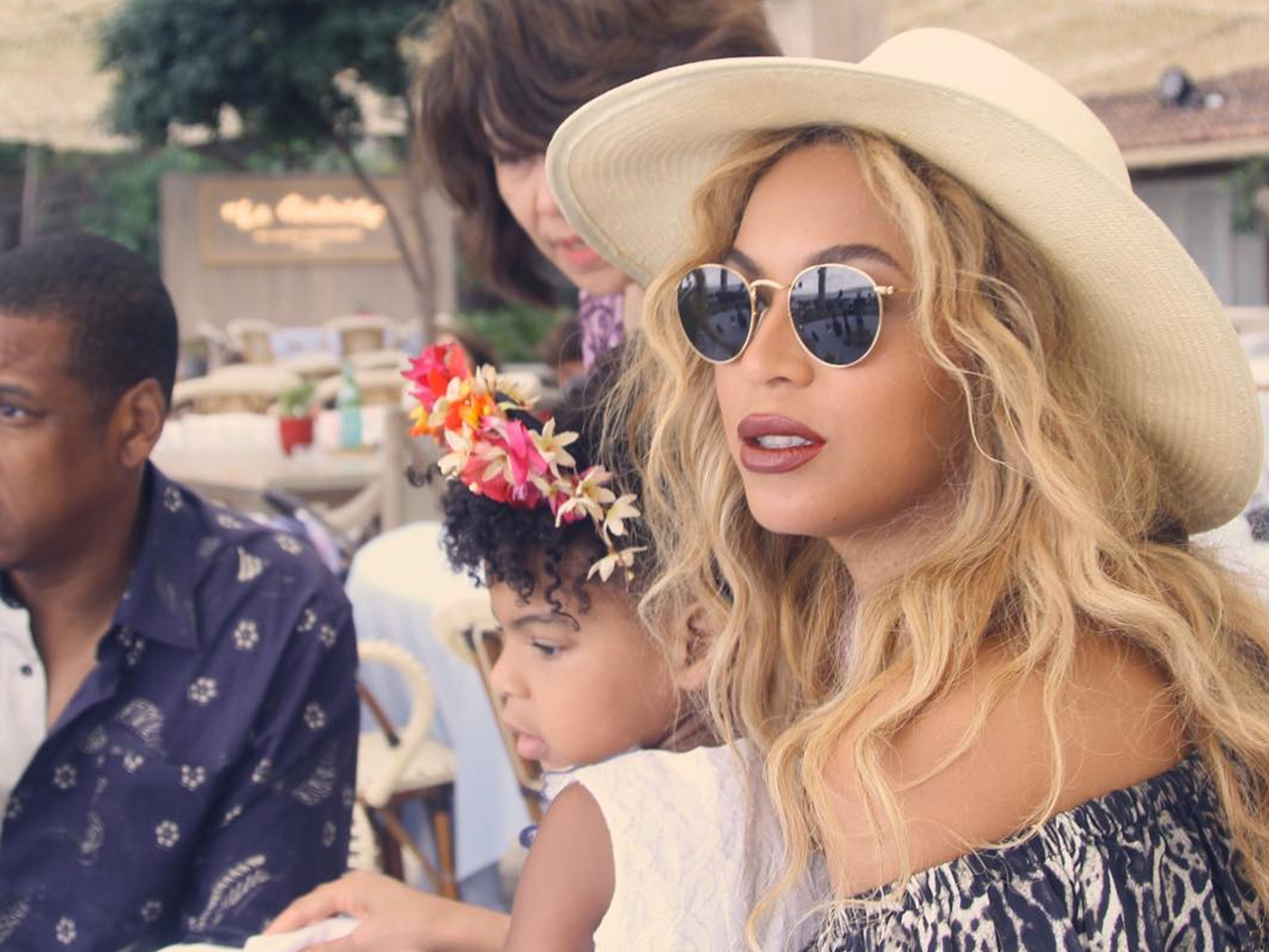 Beyonce sits outside with daughter Blue Ivy in her lap.