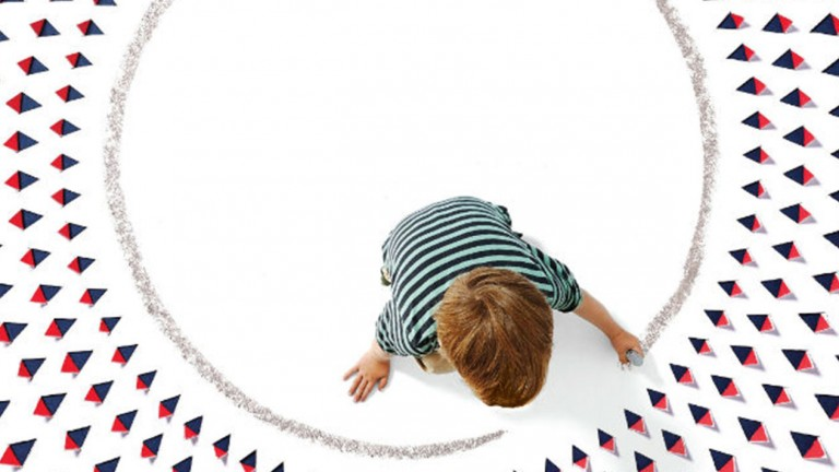 Young boy drawing a circle around himself on the ground