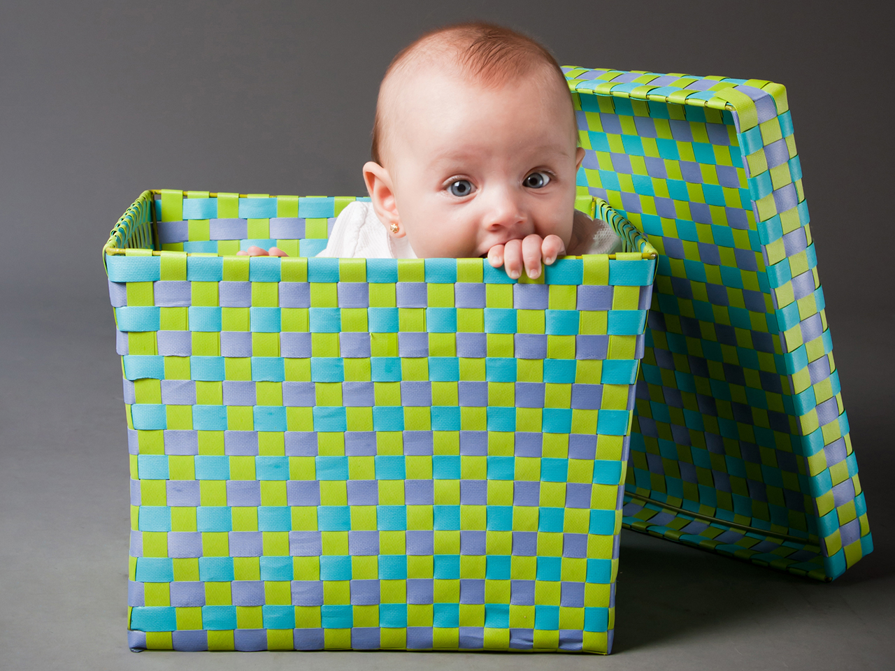 Baby sitting inside a colourful woven box