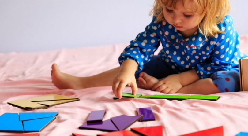 Toddler sitting on a bed solving a puzzle