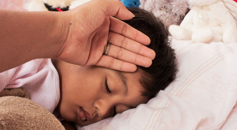 Mom touching forehead of boy in bed with a fever