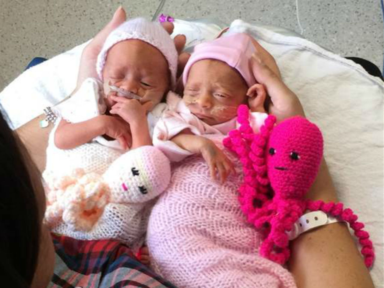 Twin preemies snuggling with crochet octopuses