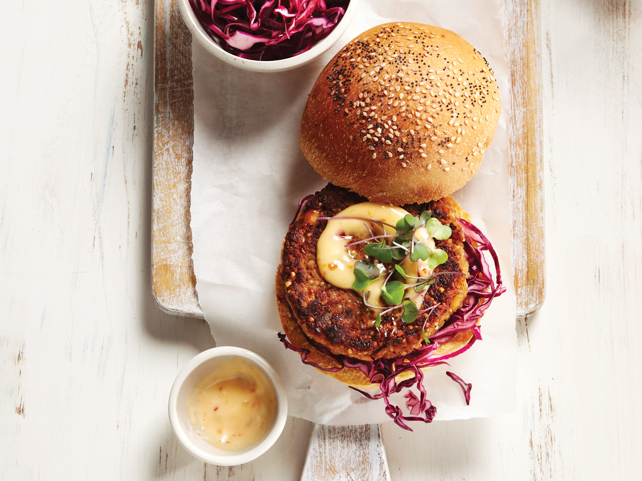 A chickpea burger topped with mayo and cabbage