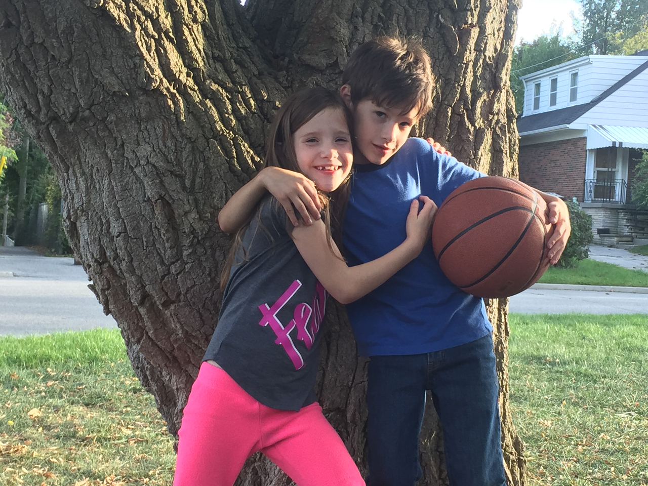 A brother and sister hugging outdoors