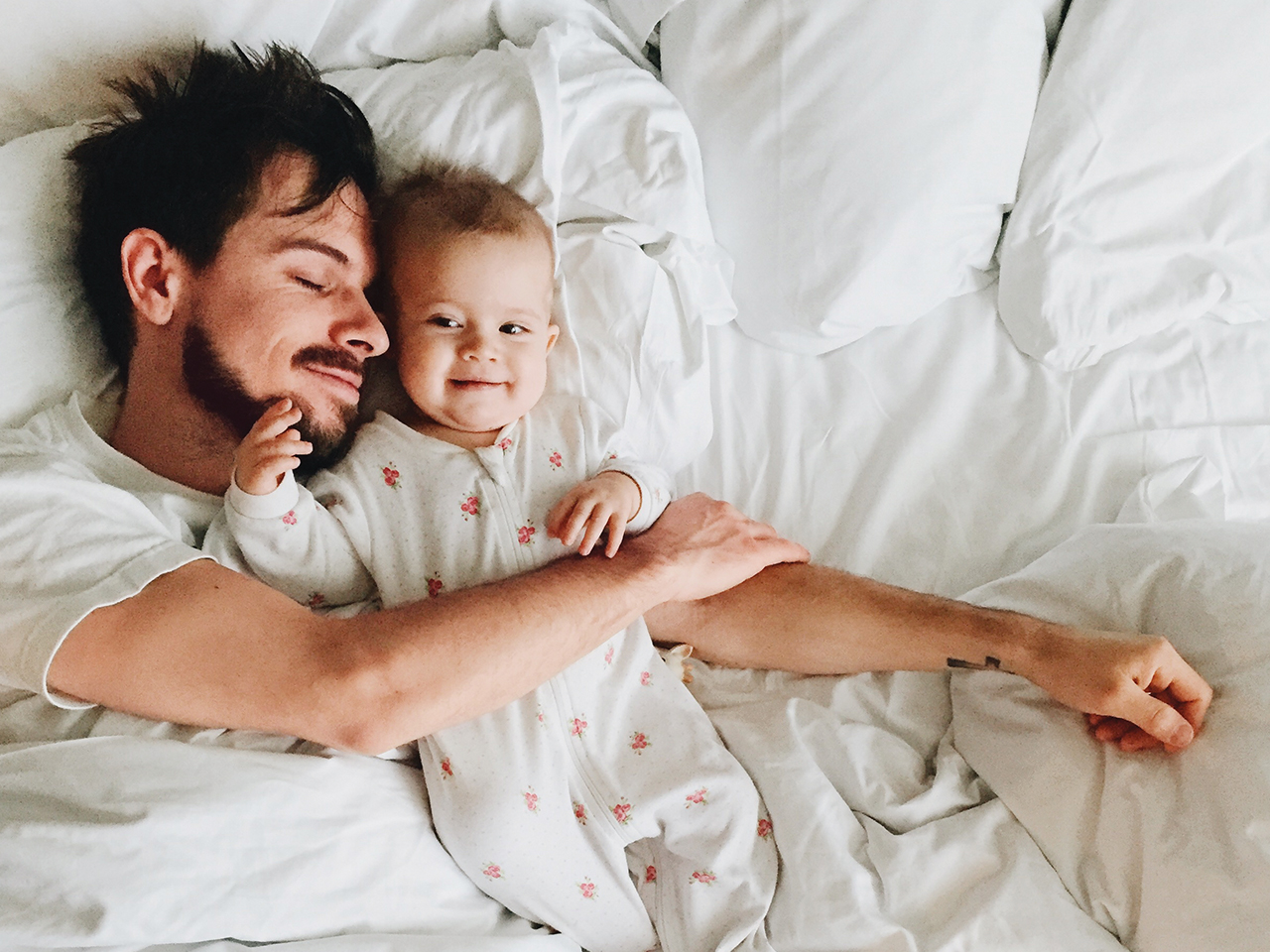 Dad and baby daughter laying in bed