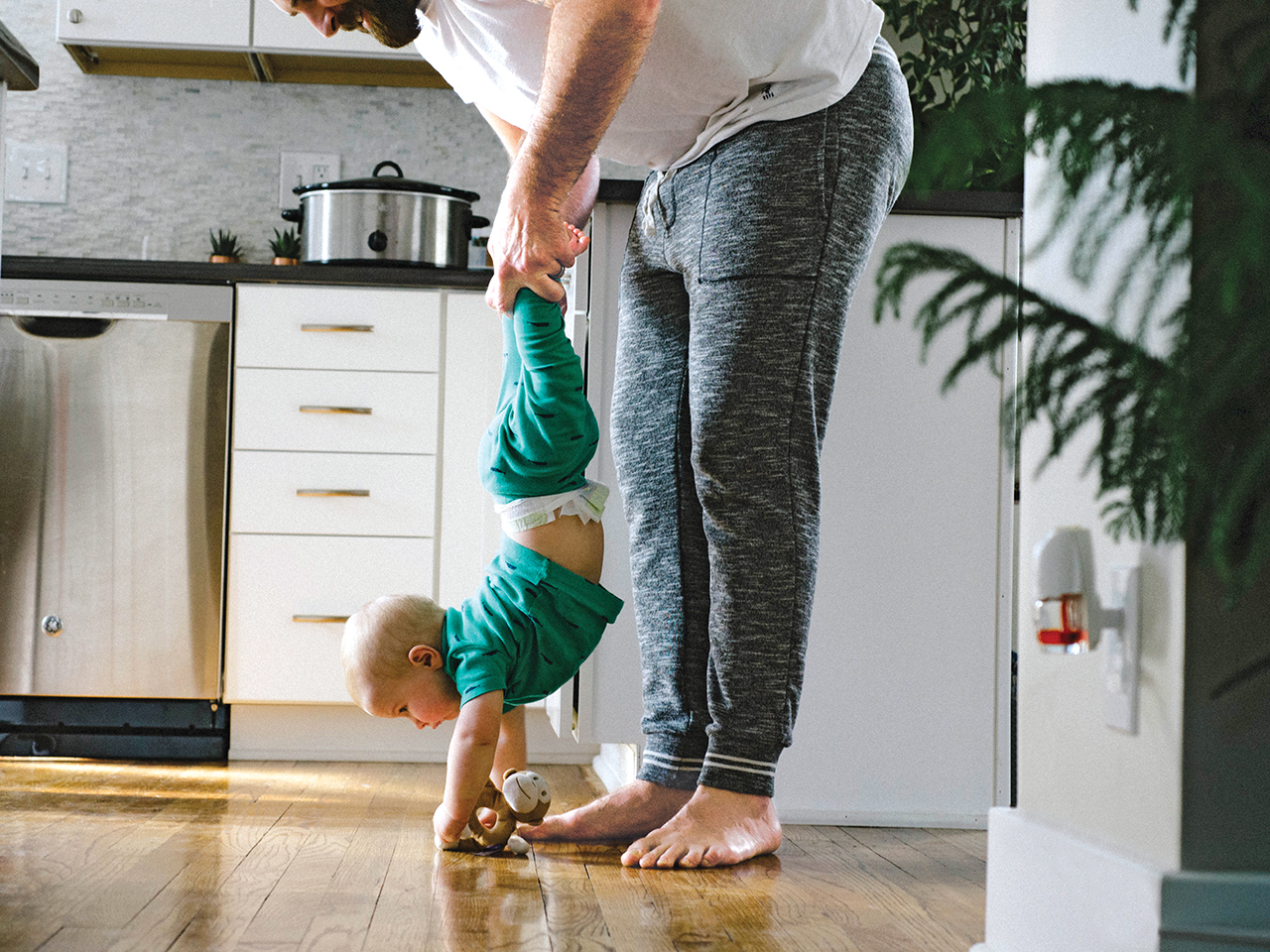 Dad holds up his son but the feet in a faux handstand