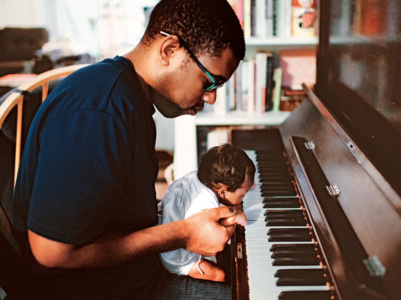 Dad sits at the piano with baby son in his lap