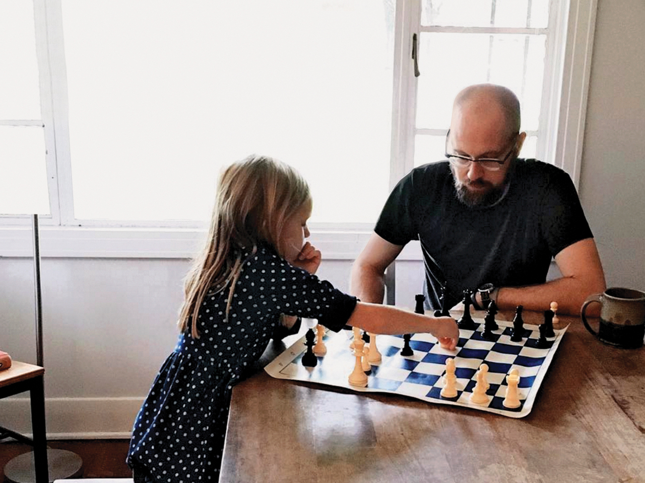 Dad and daughter playing a game of chess