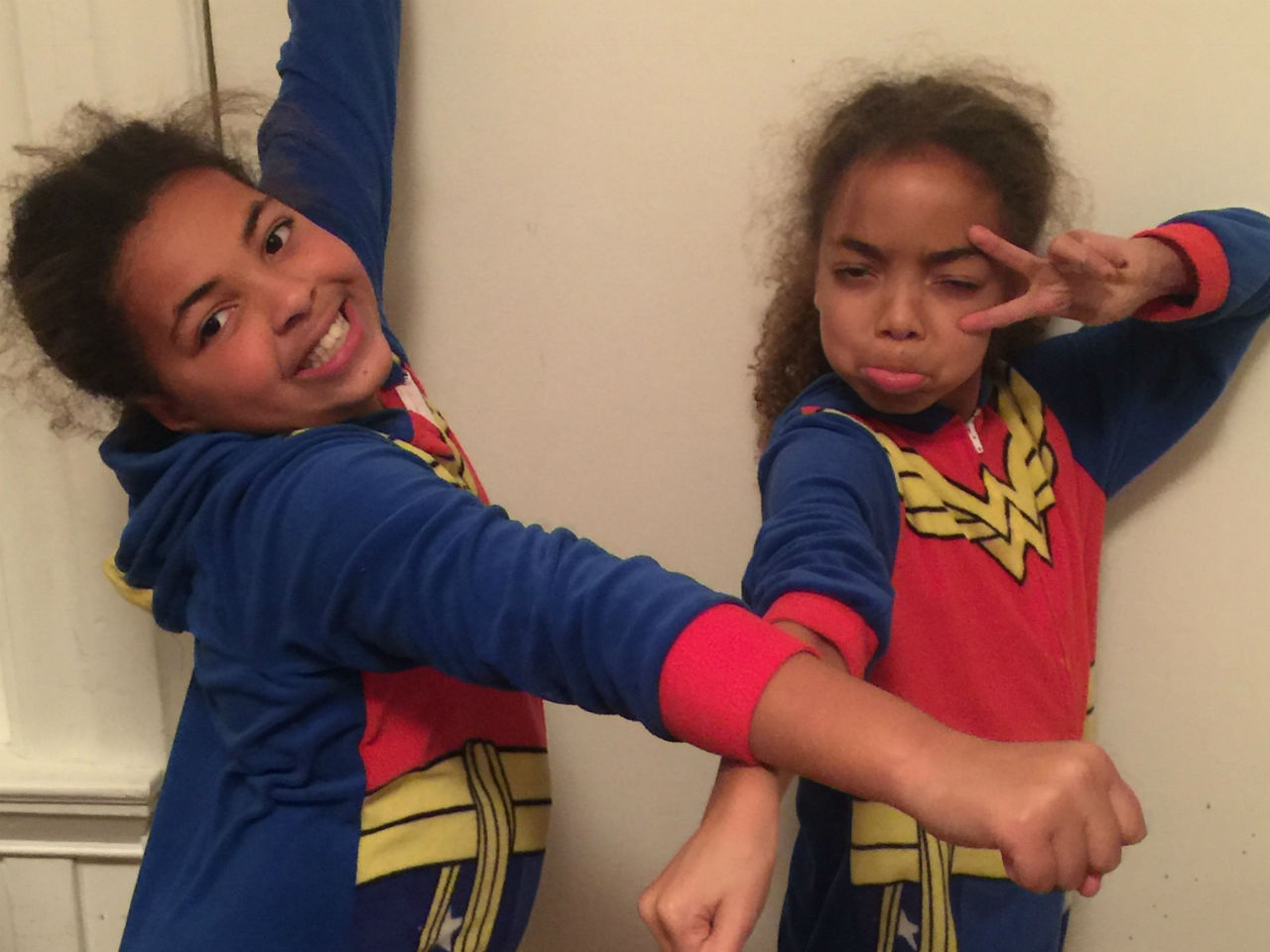 Nancy Netherland's two daughters with chronic illnesses wearing superhero pyjamas