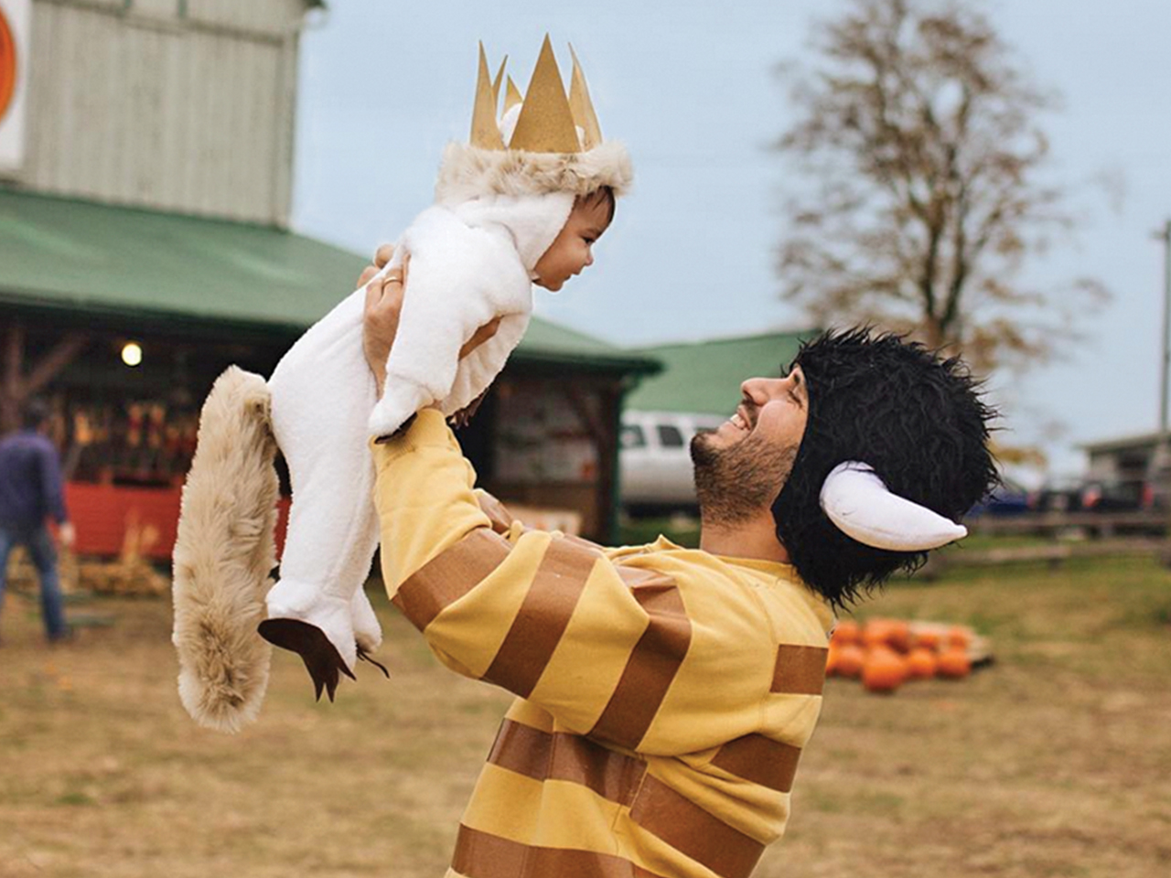 Dad lifting up daughter in the air. They are dressed as characters from Where the Wild Things Are