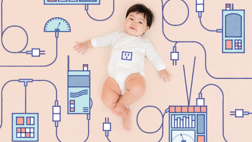 a little baby surrounded by digital equipment.
