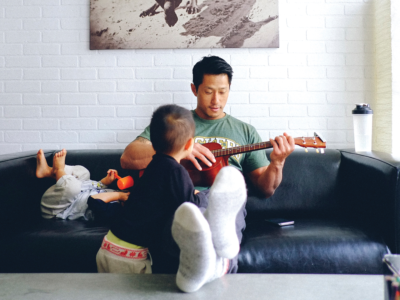 Dad sits on the couch with a ukulele and his two sons