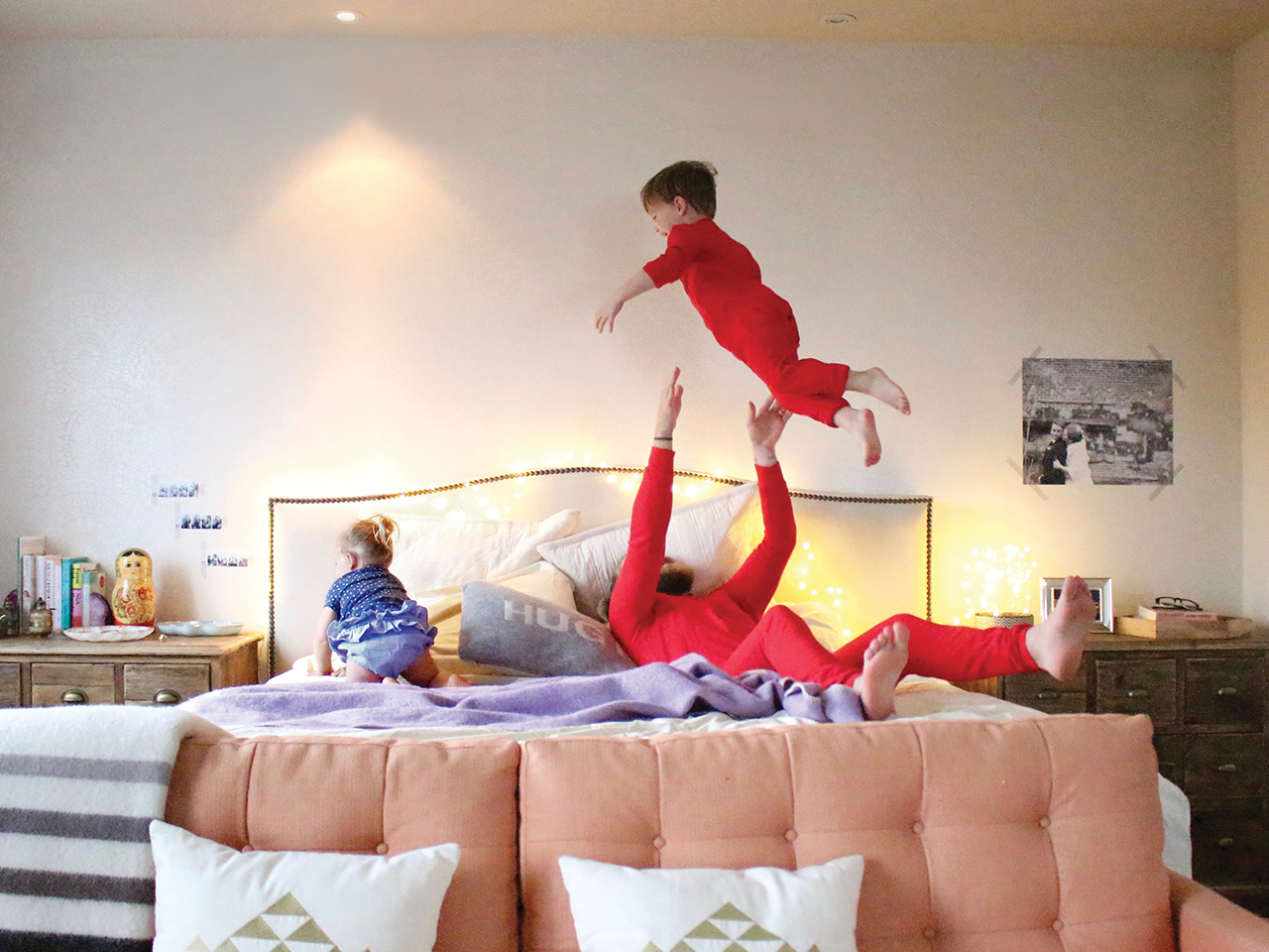 Dad and two kids in playing in bed. Dad is throwing one kid up in the air.