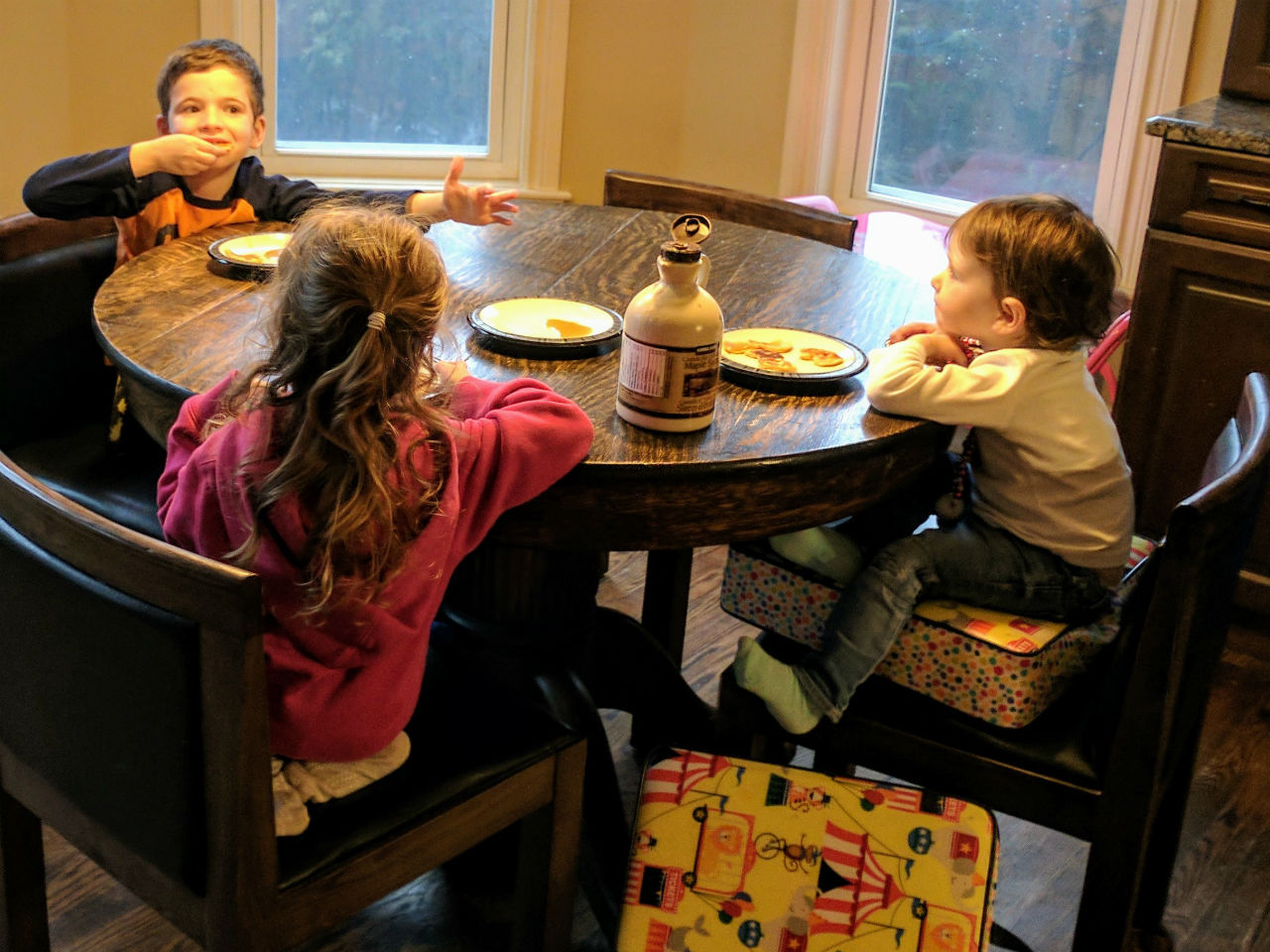 children eating pancakes at dinner table