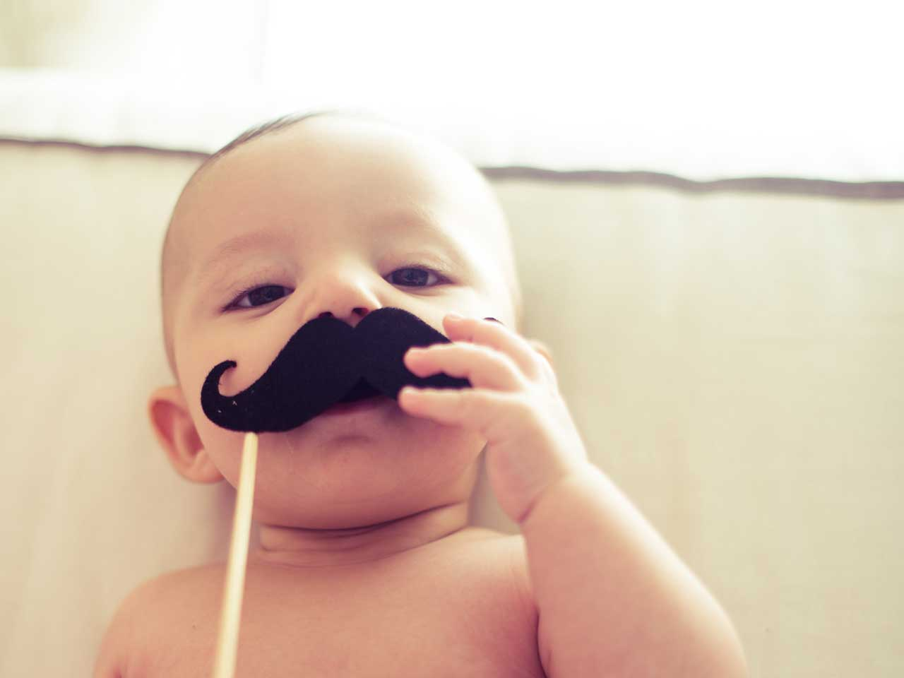 Baby holding up a fake moustache