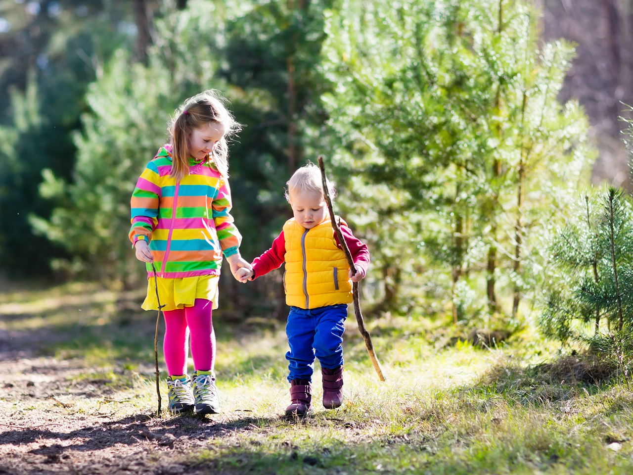 Siblings hike through down a wooded trail holding hands