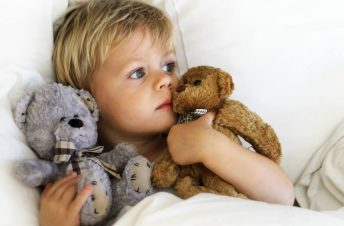 A little boy in bed with his teddy bears