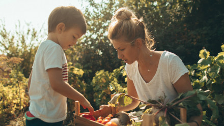 A woman and a little boy looking at vegetables they grew in their garden