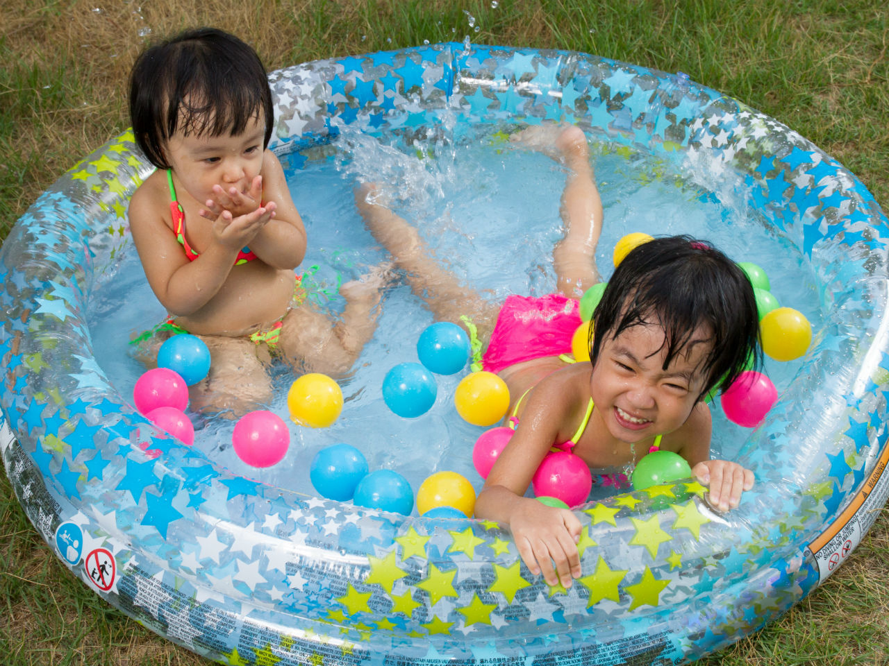 Two little girls playing in a blow up pool with neon balls