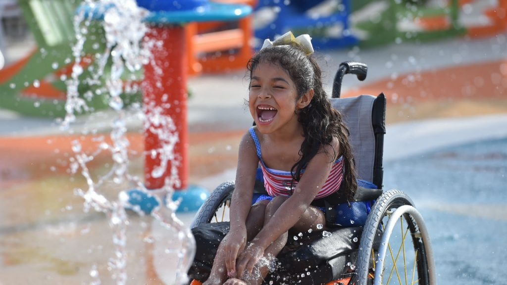 A little girl laughing and splashing at the waterpark