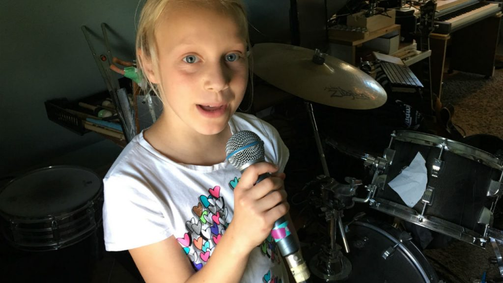 Young girl singing into microphone in front of drum kit