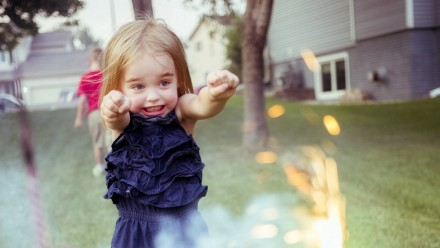 A little girl looking excited at sparklers