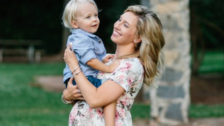 A pregnant woman holding a blonde little boy
