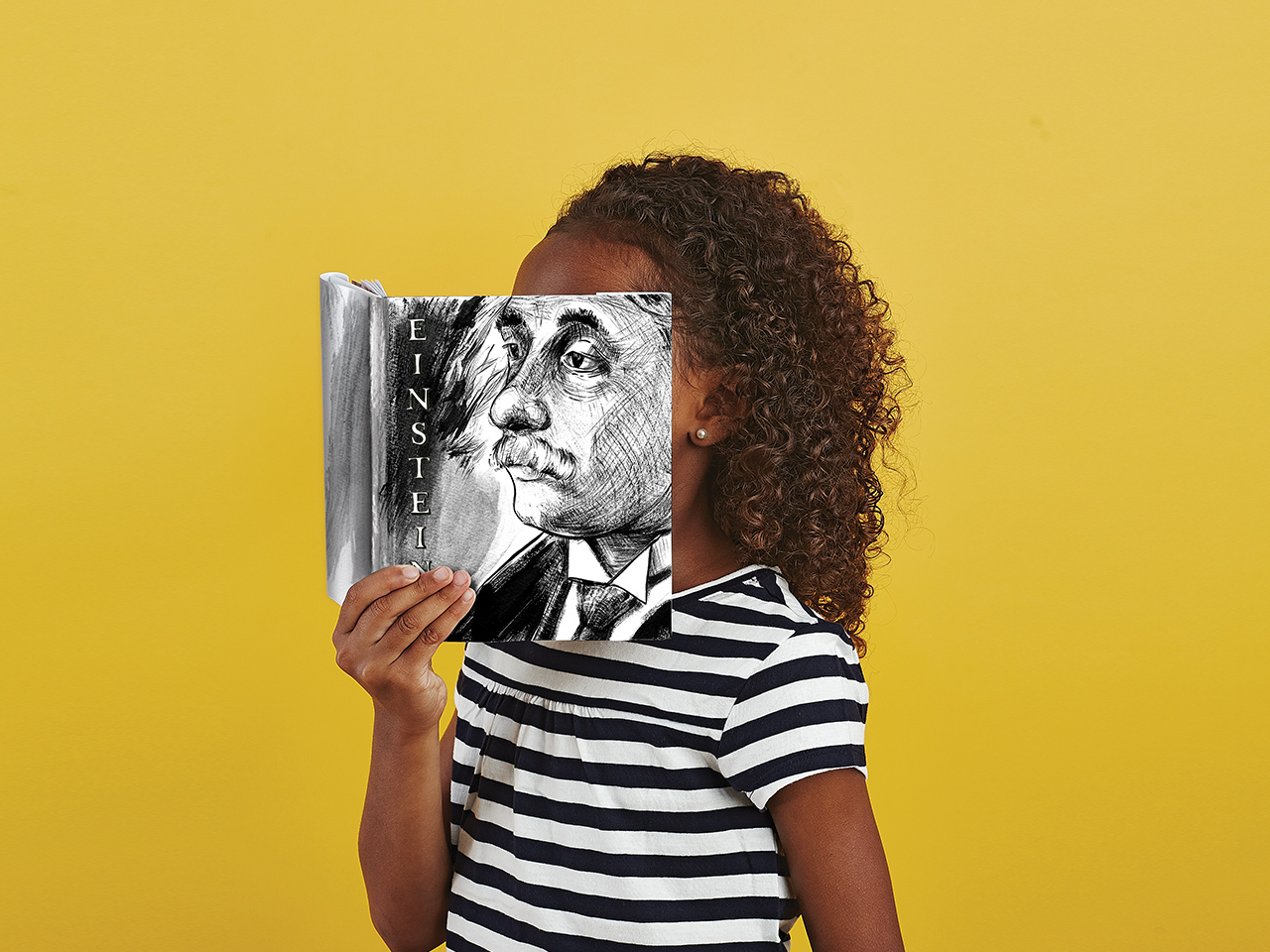 Girl holding a book in front of her face that has Einstein's face on it.