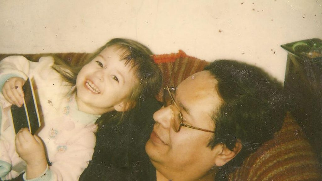 Older snapshot of a little girl laying on top of her dad on the couch, smiling