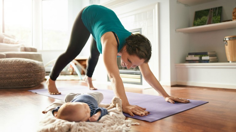 Mother does yoga while keeping an eye on her newborn baby