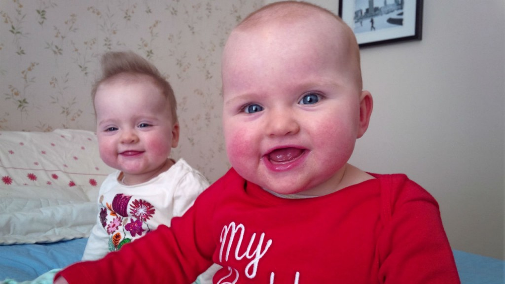 Twins babies smiling on bed