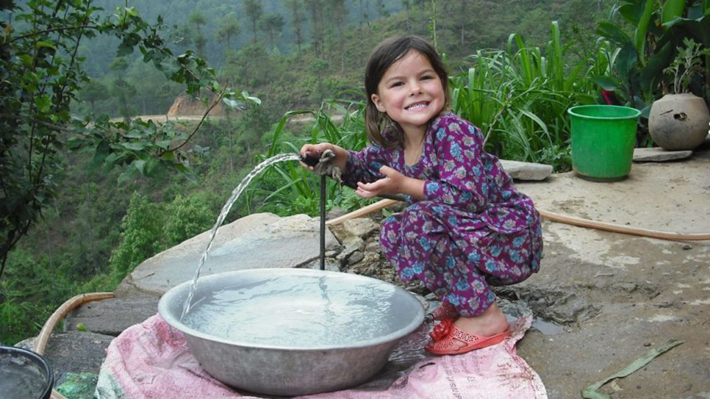 little girl with water hose in Nepal