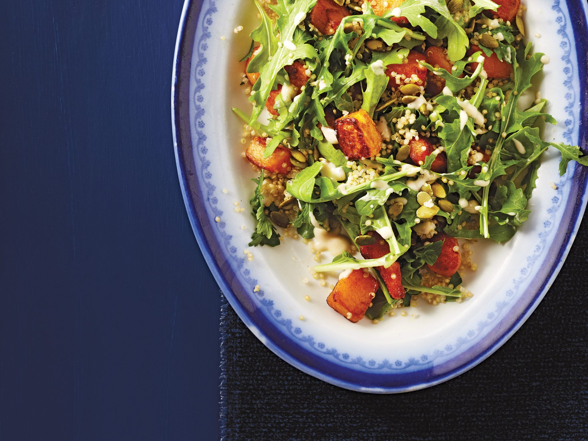 plate of arugula salad with squash, quinoa and seeds