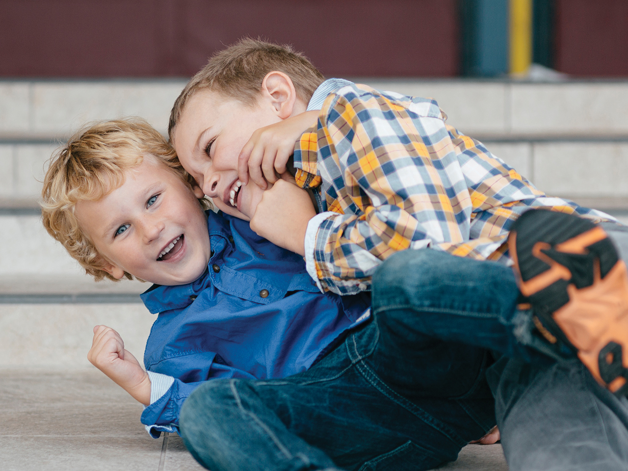 two boys play fighting on the ground laughing