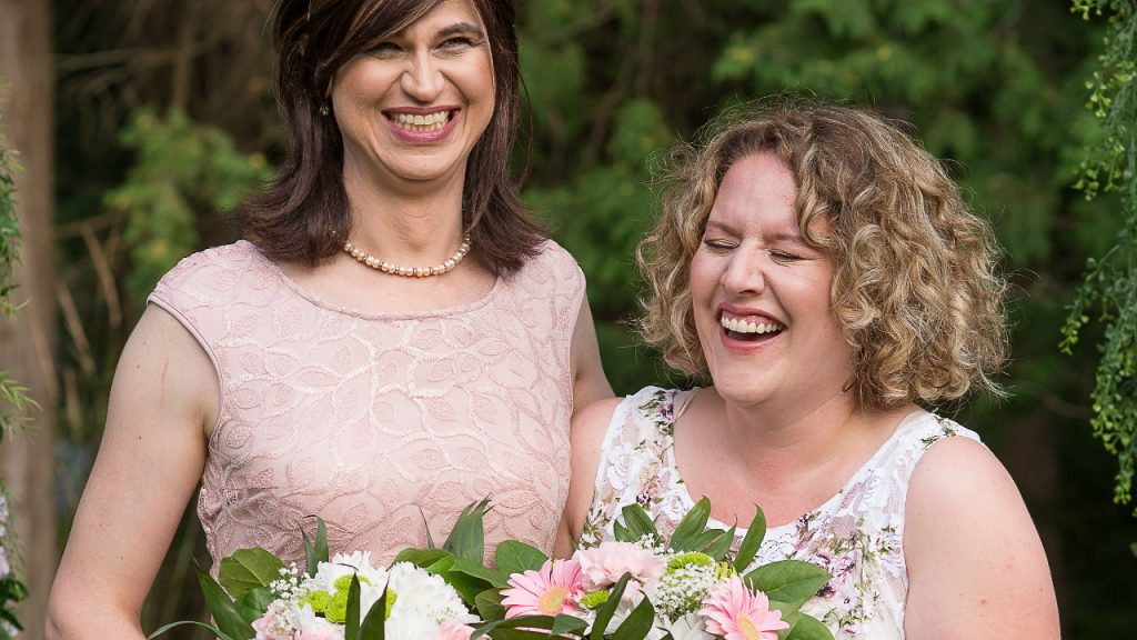 transgendered woman and wife smiling for a photo with bouquets in their hand