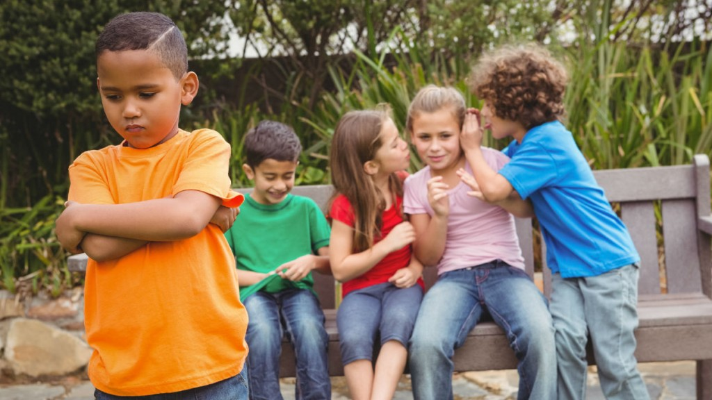 group of kids whispering to each other and excluding one boy out of the group
