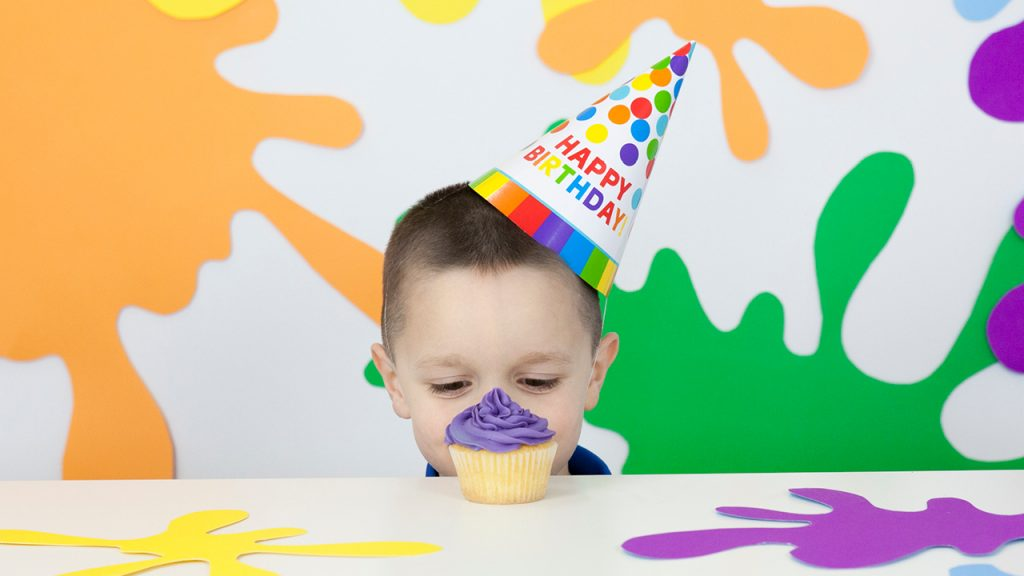 Little kid wearing a party hat and looking at a cupcake with purple frosting. Around him, the walls and table are decorated with colourful paint splatters made of paper