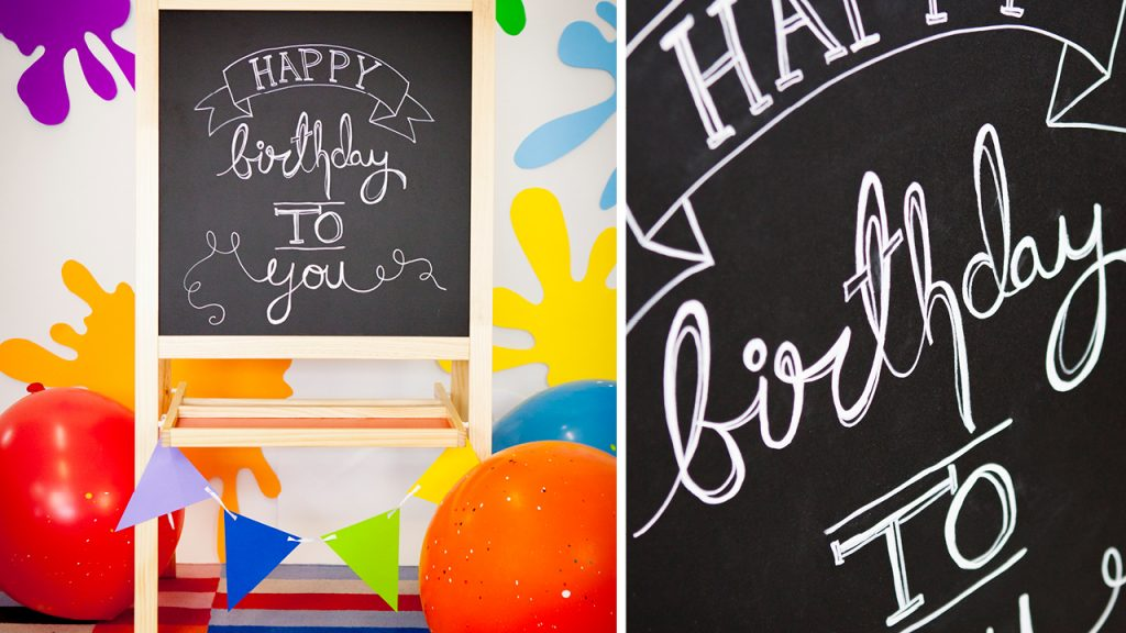Chalkboard that reads Happy Birthday to you. The board is surrounded by colourful decorations like a garland of flags, large balloons with glitter and paper paint splatters