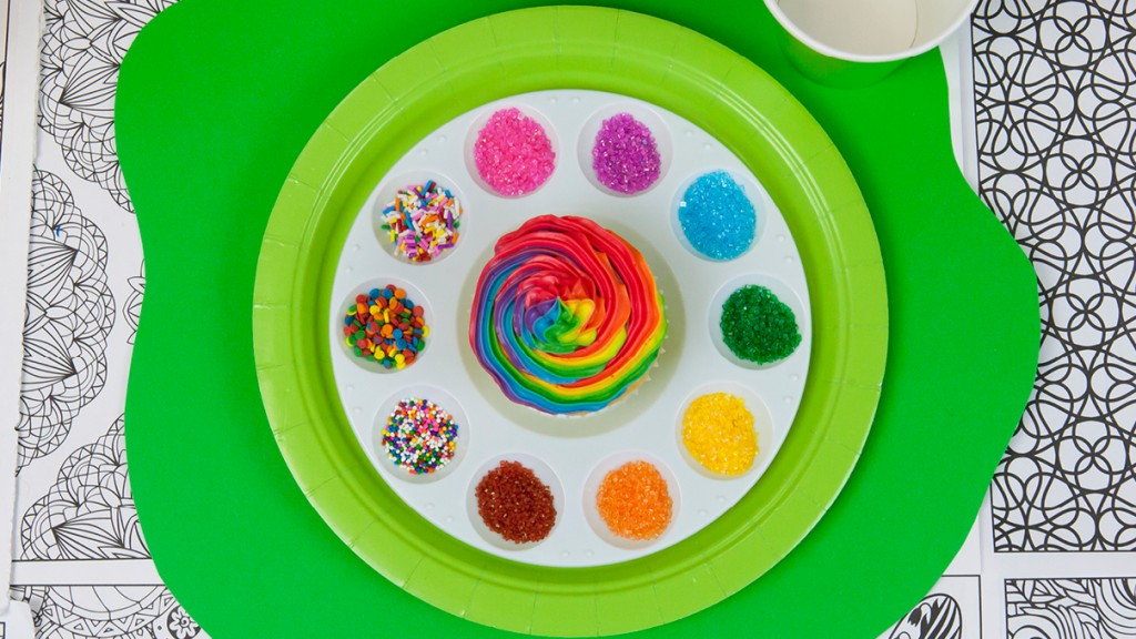 Place setting with a cupcake surrounded by a variety of sprinkles and toppings laid out on a paint palette