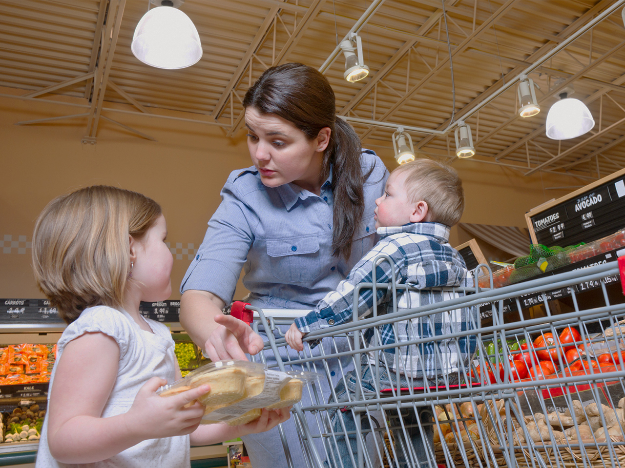 mom saying no to her daughter holding packaged cakes at the grocery store while toddler sits in cart