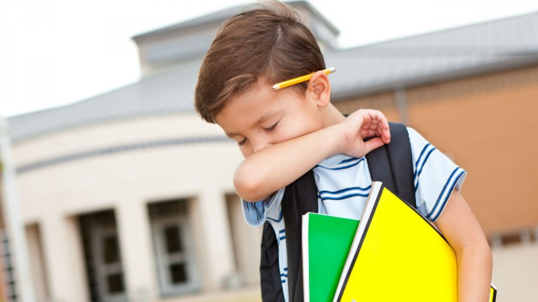 boy sneezing into his arm while holding his school book