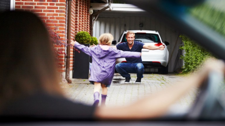 little girl running to her father with arms open, as mother watches after dropping the daughter off.