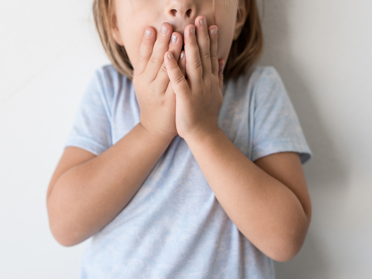 Child with her hands covering her mouth