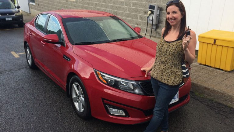 woman poses in front of a red car holding up her keys and smiling
