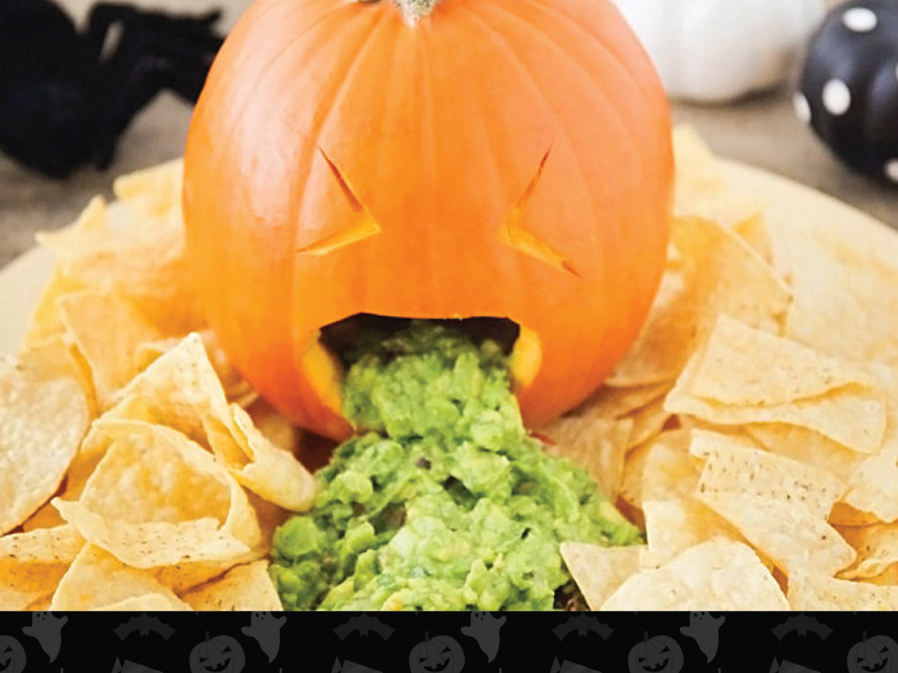 pumpkin barfing guacamole onto a platter of chips