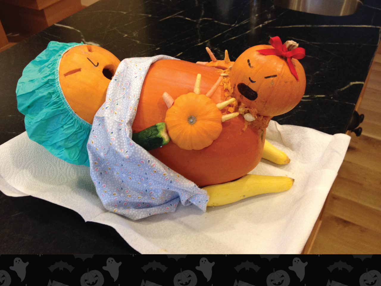 pumpkin carved as pregnant woman wearing hospital scrubs and giving birth
