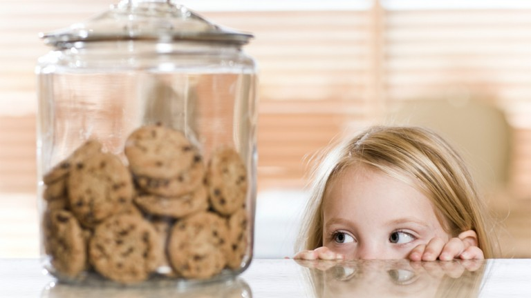 child trying to sneak chocolate chip cookies off the counter