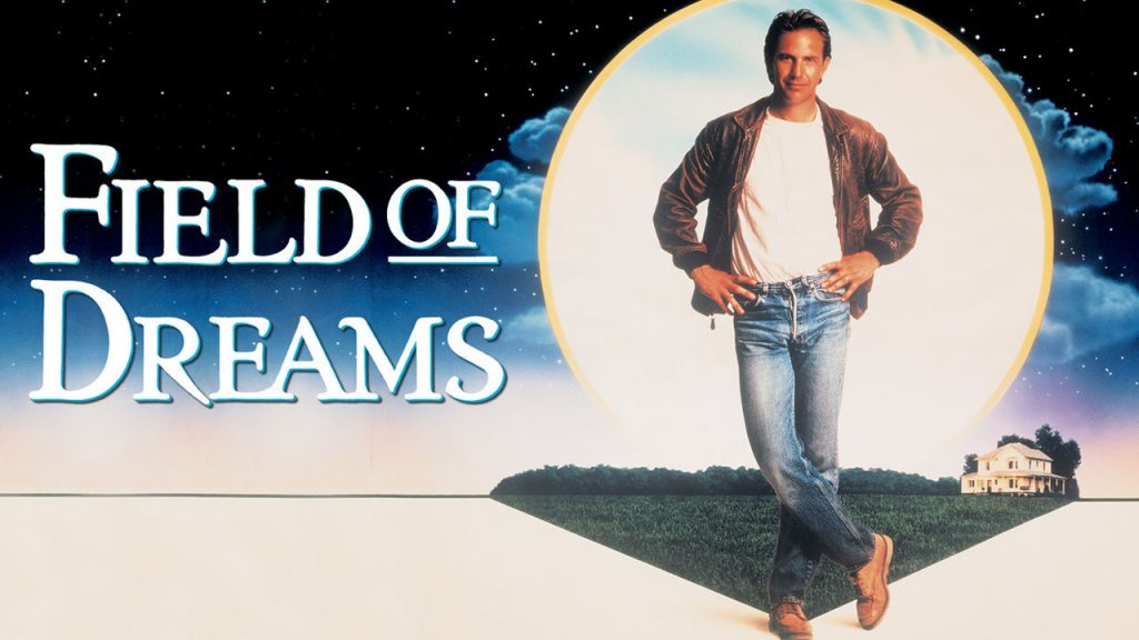 Promo image for the 80s movie Field of Dreams Shows a man wearing a brown leather jacket standing in front of a field with his hands on his hips and his leg crossed. In the background it's nighttime